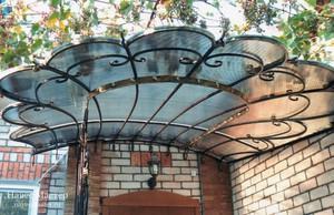 Навес над крылечком из поликарбоната с кованым каркасом — самый красивый, но и самый дорогой